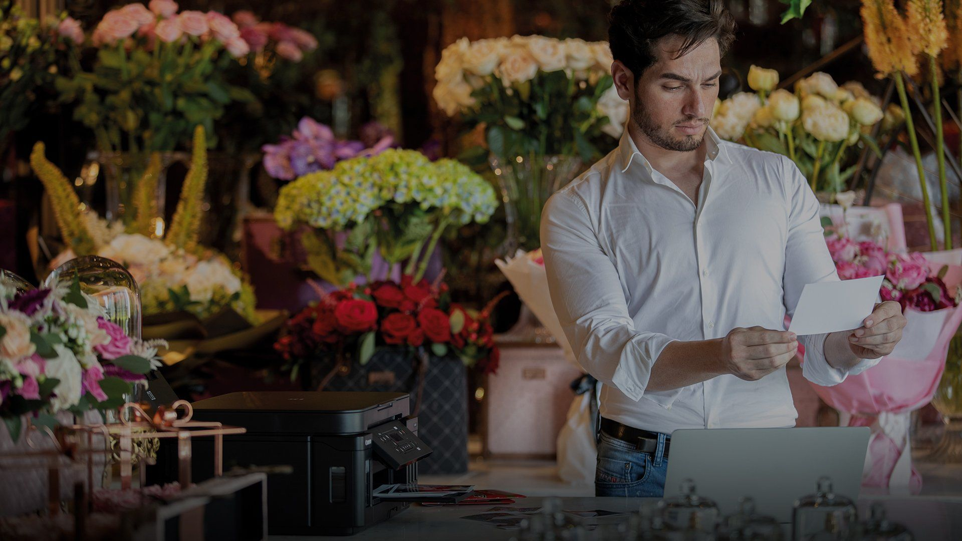 In a room filled with bouquets of flowers, a man holds a print he has made using a Canon PIXMA G6040 that can be seen on the table in front of him.